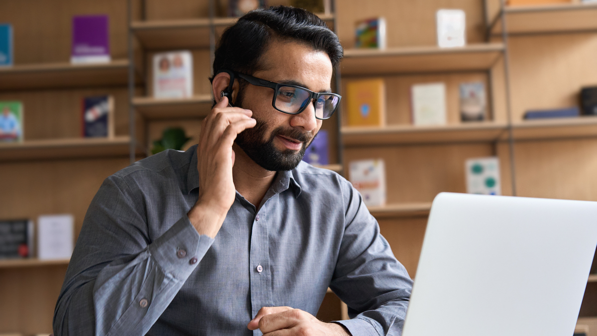 Indian remote consultant wearing headset with laptop    Canada Express Entry
