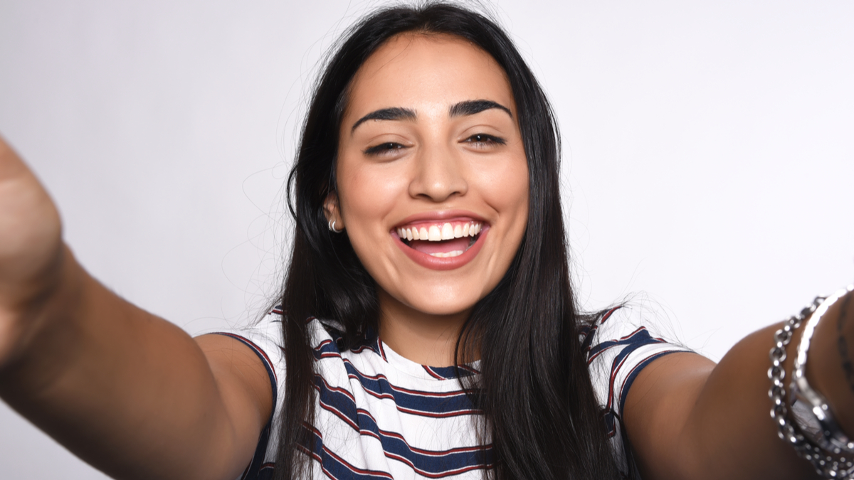 smiling woman with arms stretched out   real or fake